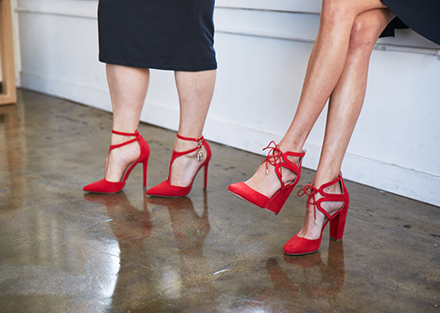 Two women wearing red court shoes.