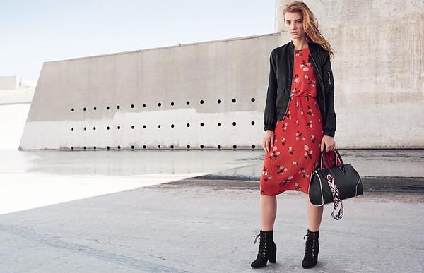 Frau im schulterfreien Midi-Kleid mit Schultertasche und Absatzsandalen.