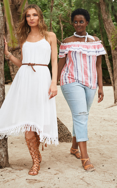 A woman wearing a white midi dress and gladiator sandals, next to a woman wearing an off-the-shoulder top, jeans and sandals.