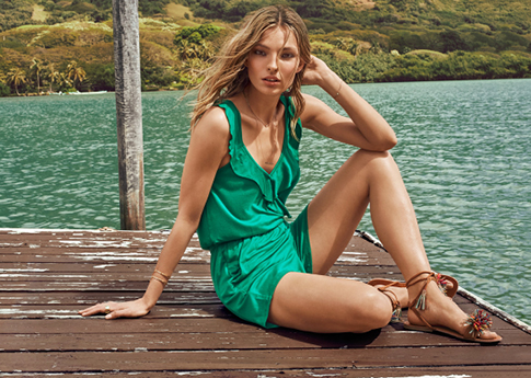 Woman wearing a green playsuit and lace-up flat sandals.