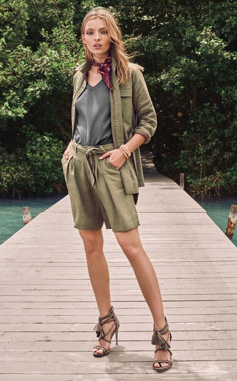Femme portant un short en lain kaki, une paire de sandales à talons vertes et une veste verte.