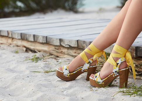 Woman wearing platform sandals in a lemon print.